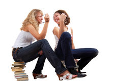 Talking on books. Two girl talking and laughing, sitting on books. Isolated on white Royalty Free Stock Photography