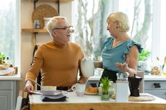 Cheerful couple talking during breakfast while sitting at the kitchen stock images