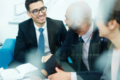 Talking at briefing. Happy businessman listening to co-worker during conversation royalty free stock photo