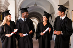 Talking about bright future. Four college graduates in graduation gowns walking along university corridor and talking Stock Image