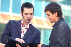 Talking Business. Two male coworkers discussing the contents of a work folder Stock Photo
