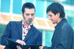 Talking Business. Two male coworkers discussing the contents of a work folder.  Blue tinted Royalty Free Stock Photos