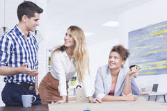 Talking about business. Group of young people talking about business plan at work Stock Images