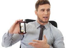 Talking businessman holding hourglass. Royalty Free Stock Images