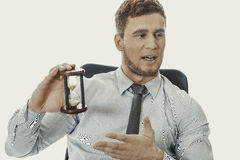Talking businessman holding hourglass. Royalty Free Stock Image