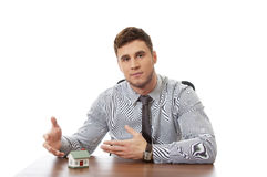 Talking businessman with house model by a desk. Stock Images