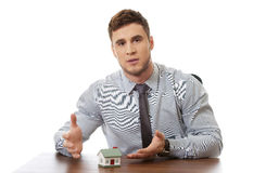 Talking businessman with house model by a desk. Stock Photos