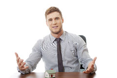 Talking businessman with house model by a desk. Stock Photography