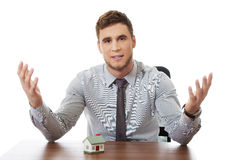 Talking businessman with house model by a desk. Stock Image