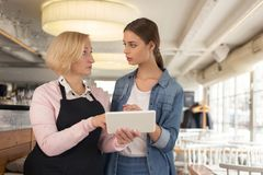 Serious waitress discussing work with her employer. Talking about cafe. Concentrated blond waitress holding a tablet and talking with her young employer Royalty Free Stock Photos