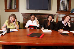 Talking on cell phone. A team of employees at work on their cell phones royalty free stock photo