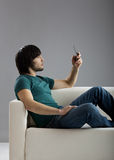 Talking at cellphone. Good-looking young man seated on the couch and talking at cellphone Royalty Free Stock Photos