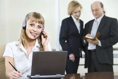 Talking with client. Portrait of beautiful smiling blond woman in gray suit touching headset on her head working on laptop and two businesspeople on the Royalty Free Stock Photo