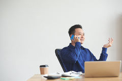 Talking with client. Smiling Singaporean businessman consulting client on the phone Royalty Free Stock Image