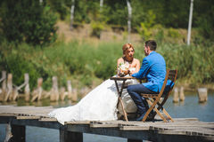 Talking Couple on Bridge. Talking couple at table on wooden bridge Stock Photography