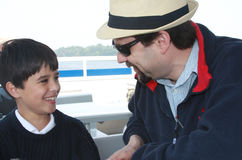 Talking with Dad. A cute llite boy is talking with his dad during on a sailboat. They are having good time together like great friends Royalty Free Stock Photos