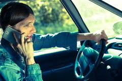 Man talking on phone while driving car. Talking while drive, danger fresh driver concept. Young man driving car using his smartphone, talking with someone stock images