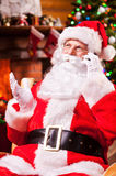 Talking with elfs. Happy Santa Claus talking on the mobile phone and smiling while sitting at his chair with fireplace and Christmas Tree in the background Stock Images