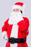 Talking with elfs. Traditional Santa Claus talking on the mobile phone while standing against grey background Stock Photos
