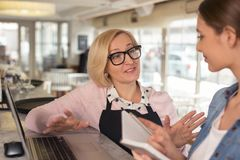 Content waitress discussing work with her employer. Talking with employer. Happy blond waitress smiling and talking with her young employer Stock Photos