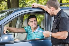 Talking with experienced policeman. Young driver is talking with experienced policeman royalty free stock photo
