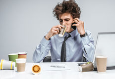 While talking intensely on a phone, manager sitting with a cup. Royalty Free Stock Photo