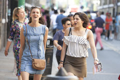 Talking and laughing hipster girls dressed in cool Londoner style walking in Brick lane, a street popular among young trendy peopl. LONDON, ENGLAND - August 25 Royalty Free Stock Photos