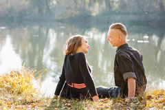 Talking and laughing. Young male and female sitting near water talking laughing having good time Royalty Free Stock Photo