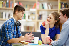 Talking at lunch break. Happy teenagers having snack and talk at break between lessons Royalty Free Stock Photo