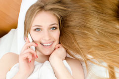 Talking on the mobile cell phone pretty blonde girl with blue eyes, red nails & white teeth lying in white bed happy smiling Stock Image