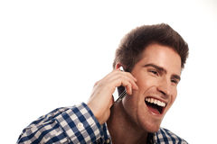 Talking on a mobile phone. Casual man smiling and talking on a mobile phone isolated over a white background Royalty Free Stock Images