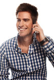 Talking on a mobile phone. Casual man smiling and talking on a mobile phone isolated over a white background Stock Image