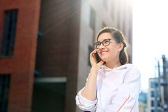 Talking on a mobile phone. Happy, smiling young woman talking on the phone stock photo