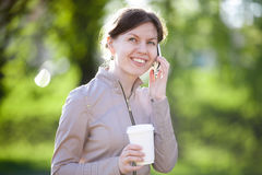 Talking on mobile phone in park Stock Image