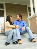 Talking About New House. Two young people talking and sit in front of their new house royalty free stock photography