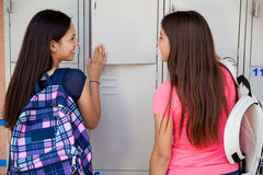 Talking next to school lockers. Pretty teenage girls talking to each other while grabbing some books from the school lockers stock photos