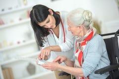 Talking old lady through medication. Talking old lady through her medication Royalty Free Stock Image