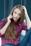Talking over the phone. Charming upset girl talking over the phone Royalty Free Stock Photos