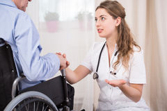 Talking with patient. Young pretty female doctor talking with her injured male patient Royalty Free Stock Images