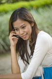 Talking on the phone. An asian girl is busy talking on the phone with a friend Stock Photos