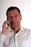 Talking on the phone. Business man in white shirt making a phone call using a head set - vertical format Stock Photography
