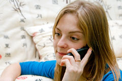 Talking On a Phone. Closeup smiling young beautiful woman talking on a phone Royalty Free Stock Photography