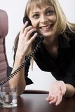 Talking by the phone. Smiling expressive blond businesswoman talking by her phone Stock Photos