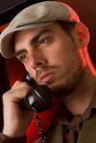 Talking on the phone. Close up of a handsome man talking on an old style telephone Royalty Free Stock Photography