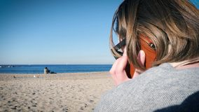 Talking on the phone at the beach. Rear view of business casual woman walking on the mobile smartphone at the Playa de Barceloneta Beach with impressive view to stock video