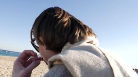 Talking on the phone at the beach. Side view of business casual woman walking on the mobile smartphone at the Playa de Barceloneta Beach with impressive view to stock video footage
