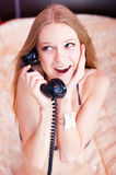 Talking by the phone in a bedroom. Pretty woman talking by the telephone on a bed in bedroom, dressed in a linen and beads royalty free stock image