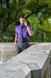Talking on Phone. Dressing in a purple shirt, gray pants and a black tie, a young handsome guy with a little beard and mustache is talking on the phone outside Royalty Free Stock Image