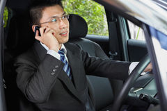 Talking on phone while driving. Chinese businessman inside car talking on cell phone while driving Stock Images