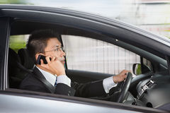 Talking on phone while driving. Chinese businessman inside car talking on cell phone while driving Stock Photo